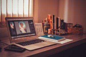 Escrivaninha com um laptop e outros acessórios de escritório.