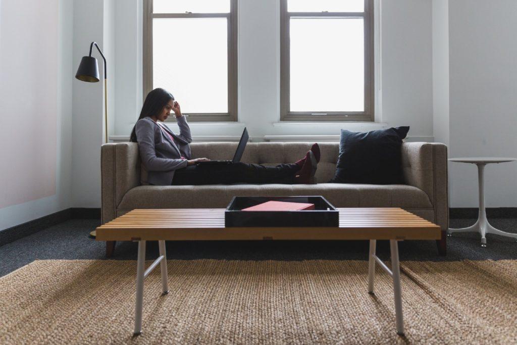 Mulher sentada em um sofá com um laptop em seu colo.
